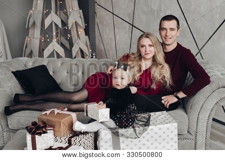 Cheerful And Jovial Family With Baby On Gray Sofa.