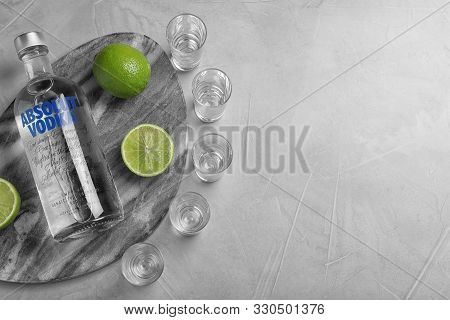 Mykolaiv, Ukraine - October 04, 2019: Absolut Vodka, Limes And Shot Glasses On Light Grey Table, Fla