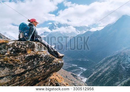 Young Hiker Backpacker Female Sitting On Cliff Edge And Enjoying The Imja Khola Valley During High A