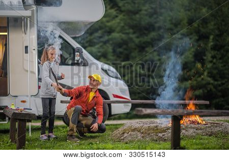 Summer Family Rv Camp. Father Having Fun With His Daughter In Front Of Campfire. Rv Class B Motorhom