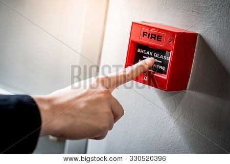 Male Hand Pointing At Red Fire Alarm Switch On Concrete Wall In Office Building. Industrial Fire War