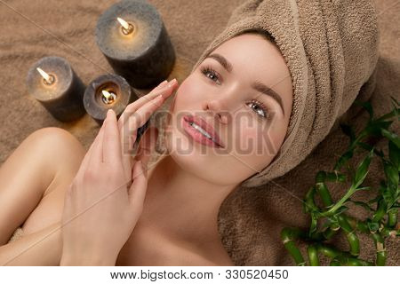 Beautiful spa woman with a towel on her head lying and touching face skin. Skincare. Beauty smiling model girl in spa salon. Skin care, acne treatment, cleansing fresh skin. Renewal cosmetics wellness