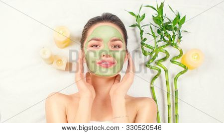 Spa Woman applying Facial green clay Mask. Beauty Treatments. Close-up portrait of beautiful girl lying down and applying facial mask in spa salon. Dayspa. Isolated on white background. Wide screen