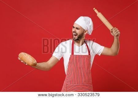 Irritated Young Bearded Male Chef Cook Or Baker Man In Striped Apron White T-shirt Toque Chefs Hat P