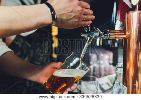 Close Up Of A Male Bartender Dispensing Draught Beer In A Pub Holding Large Glass Tankard Under A Sp