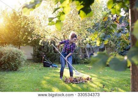 Pretty Young Woman Raking Leaves In Garden With Mower In Background