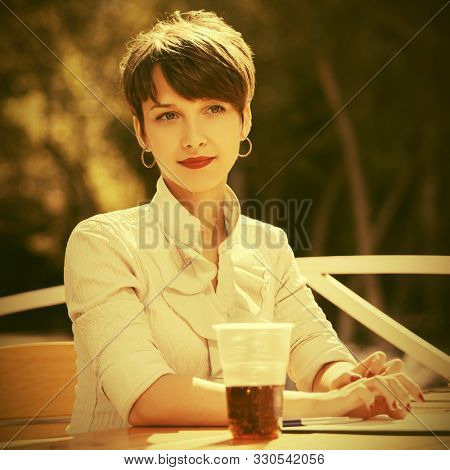 Happy young business woman working at sidewalk cafe Stylish fashion female model in white shirt with pixie hairstyle