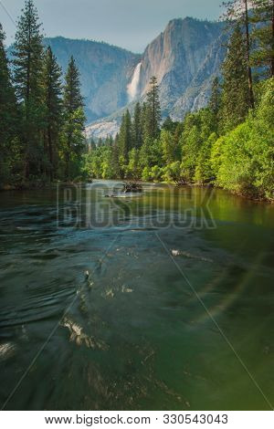 View Of Yosemite Falls From The Bridge Above Merced River In Yosemite Valley National Park, Californ