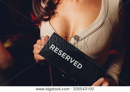 Decollete, female breast. Neckline black dress and fur collar. plate inscription reserved poster