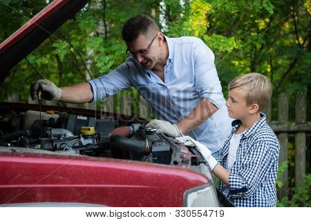 Father And Son Are Repairing The Car Outdoors. Auto Repair Concept.