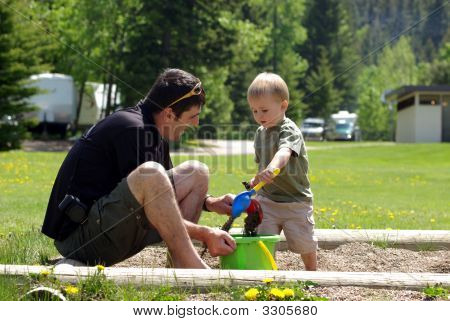 Father And Son Playing In Sandbox At Park
