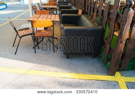 Outdoor Recreation Area - Wooden Tables And Chairs And Leather Chairs Against A Wooden Fence.