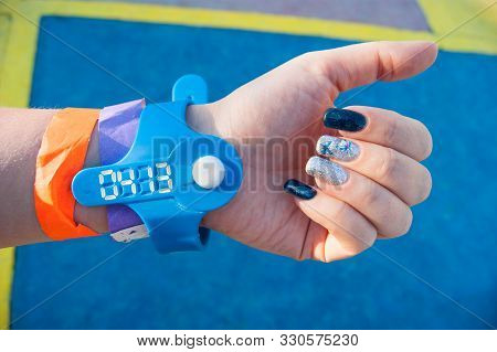 The Mood Color Is Blue - A Female Hand Against The Blue Floor In Colored Bracelets From The Water Pa