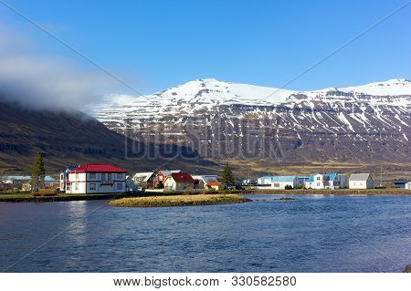 Houses In Sea Harbor Of Norther Iceland With Snowy Mountains Nearby. Inhabitable Icelandic Landscape