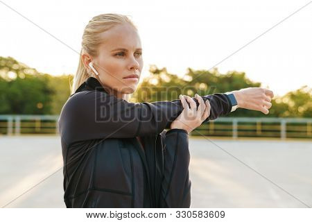 Image of concentrated sportswoman wearing tracksuit and earpods doing workout outdoors