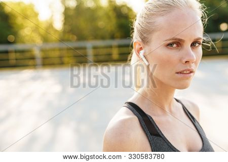 Image closeup of beautiful sportswoman wearing tracksuit and earpods walking outdoors