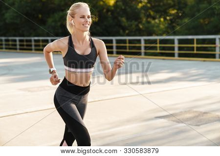 Image of caucasian fitness woman wearing tracksuit and earpods running outdoors