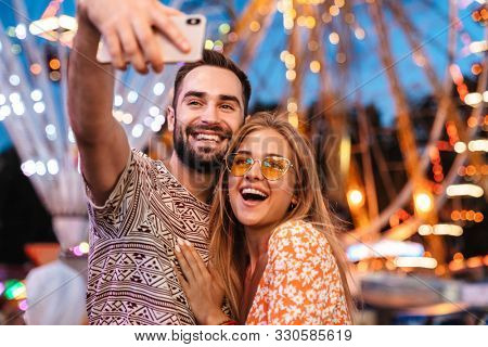 Image of a pleased positive loving couple walking outdoors in amusement park take a selfie mobile phone.