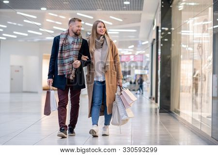 Young casual couple with paperbags looking at clothes in shop window while passing by after shopping