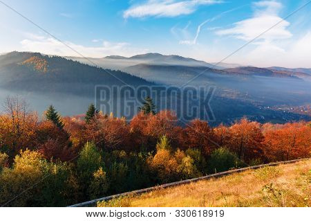 Foggy Sunrise In Carpathian Mountains. Stunning Nature Scenery In Fall Season. Trees In Red And Oran