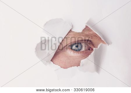 An Eye Of Gray-blue Color Looks Through A Hole In White Paper. The Concept Of Secrecy, Peeping. Mini