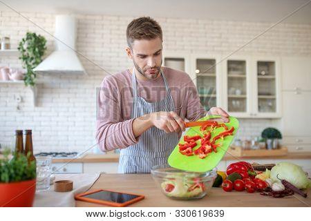 Bearded Handsome Man Cooking Veggie Salad For Dinner