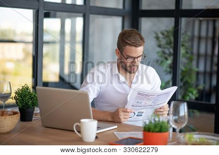 Businessman Reading Newspaper In The Morning While Sitting
