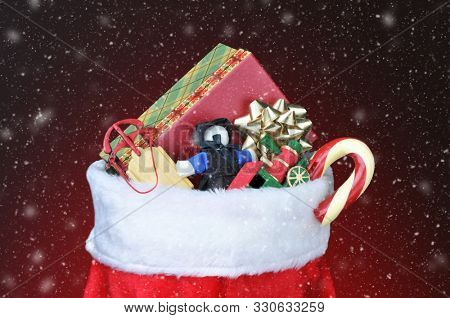 Christmas Stocking filled with toys - Light to dark red background with snow effect.