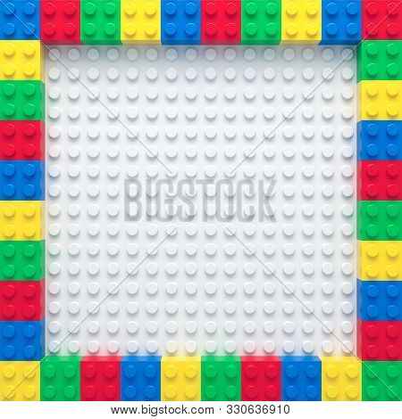Frame Of Colorful Toy Bricks On White Construction Plate
