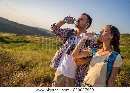 Couple Is Hiking In Mountain. They Are Drinking Water.