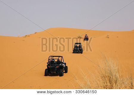 Off Road Buggys Crossing Dunes In The Desert. Rally Raid Adventure.