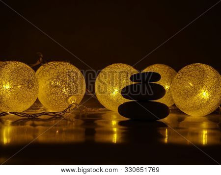 Silhouette Stack Of Zen Stones On Abstract Dark Background Of Christmas Garlands. Relax Still Life W