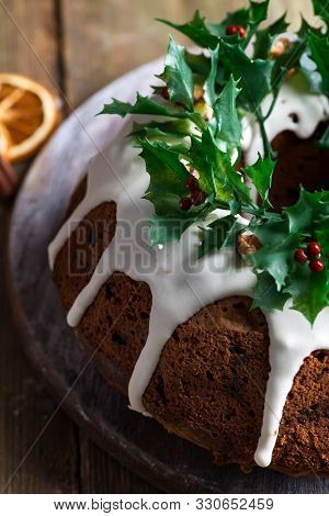 Christmas Homebaked Dark Chocolate Bundt Cake Decorated With White Icing And Holly Berry Branches Cl