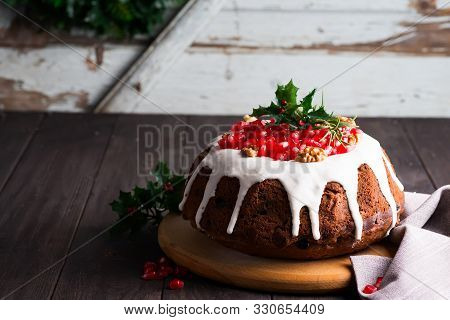 Christmas Homebaked Chocolate Cake Decorated With White Icing And Pomegranate Kernels Against The Ba