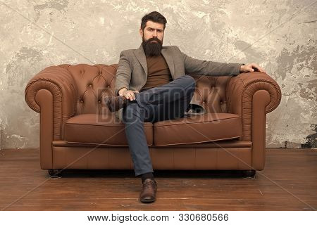 poster of Rent apartment. Bearded man with confident face sit leather couch. Loft interior apartment. Businessman realtor work. Furniture shop. Hipster realtor loft style apartment. Realtor and rental service.