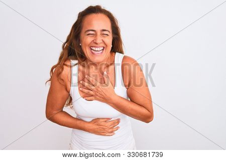 Middle age mature woman standing over white isolated background smiling and laughing hard out loud because funny crazy joke with hands on body.