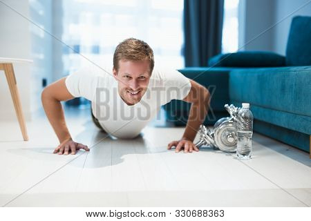 Young Handsome Man Doing Pushups During Workout At Home Looking Happy Sporty And Healthy Lifestyle