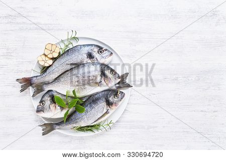 Four Fresh Royal Dorades On A Dish On White Wooden Background. Healthy Food Concept. Top View, Copy