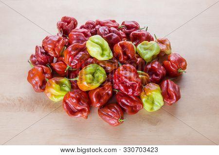 Red Hot Chilli Pepper Scotch Bonnet Caribbean Antillais On Wooden Background Colourful