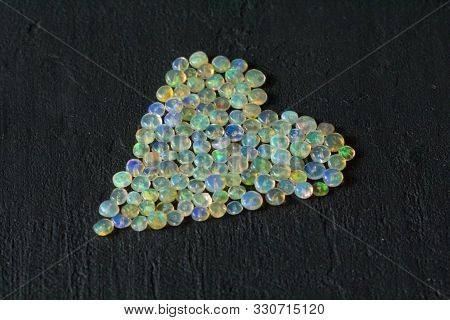 Opals Gemstone From Ethiopia Lies On Black Background. White Fire Opals With Rainbowlike Fire. Natur