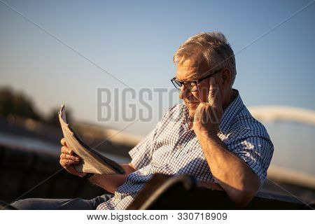 Outdoor Portrait Of Senior Man Who Is Reading Newspapers.