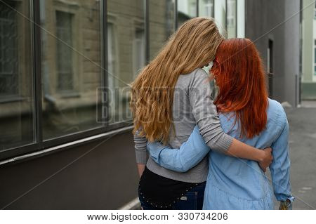 Same-sex Relationships. A Happy Lesbian Couple Walked Along The Street And Gently Hugged Each Other