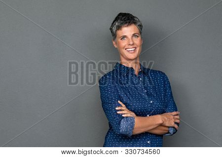 Isolated portrait of successful businesswoman looking at camera. Portrait of happy mature woman standing isolated over gray background. Confident business woman smiling with copy space.