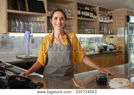 Mature woman barista standing behind the bar counter in coffee shop and looking at camera. Smiling small business owner smiling behind the counter. Portrait of beautiful waitress wearing apron.