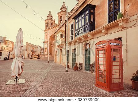 Marsaxlokk, Malta: Traditional Red Color Phone Booth On Historical Square With Church And Beautiful