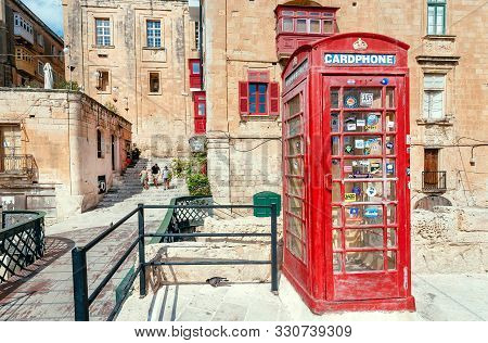 Valletta, Malta: Tourists Walking Down Street With Traditional Red Color Phone Booth And Historical