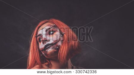 Pretty Young Girl With Scary Dead Doll Makeup Is Posing For Photographer At Dark Photo Studio.
