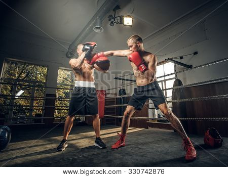 Two Brutal Sporty Boxers Have A Sparring On Boxing Ring At Dark Gym.