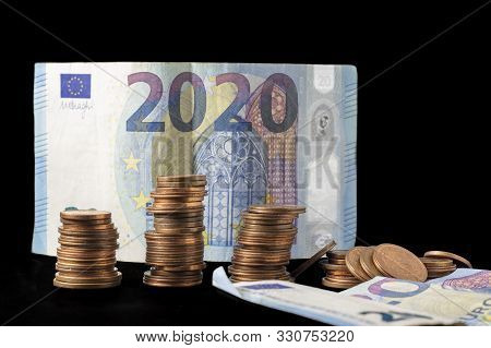 New Fiscal Year 2020 Represented With Euro Bills And Coin Stacks Isolated On Black. Conceptual Image