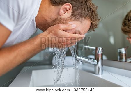 Face wash man in bathroom washing cleansing for acne facial treatment in sink splashing cold water onto face. Men beauty skincare lifestyle.